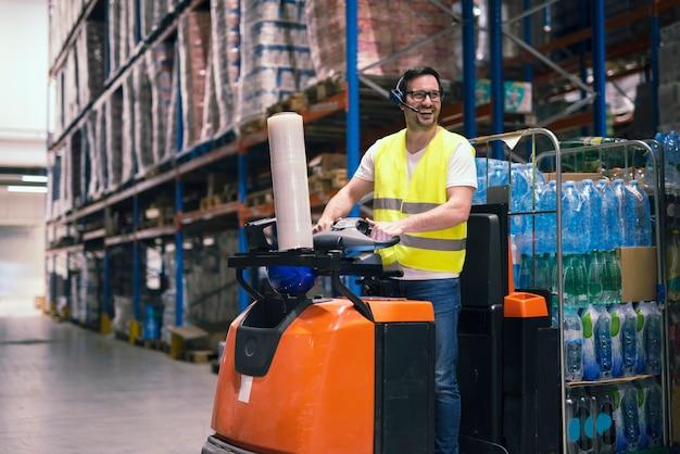 Trabalhador de armazém profissional com equipamento de comunicação de fone de ouvido, conduzindo empilhadeira e realocando pacotes no centro de armazenamento