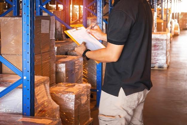 Trabalhador de armazém segurando a prancheta, fazendo gestão de estoque, verificar estoque de caixas de carga