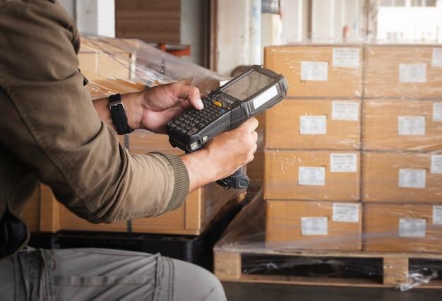 Trabalhador de armazém segurando leitor de código de barras no armazém ferramentas de computador para gerenciamento de estoque