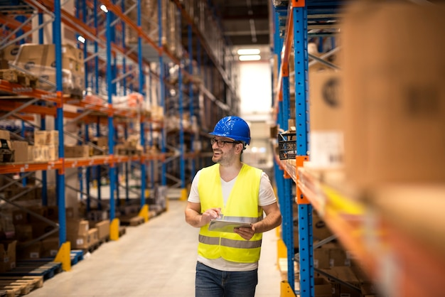 Trabalhador de armazém segurando um tablet e verificando o estoque em um grande centro de armazém de distribuição