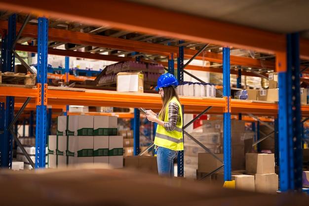 Trabalhador de armazém sorridente verificando pacotes na prateleira e estoque de produtos em seu computador tablet.