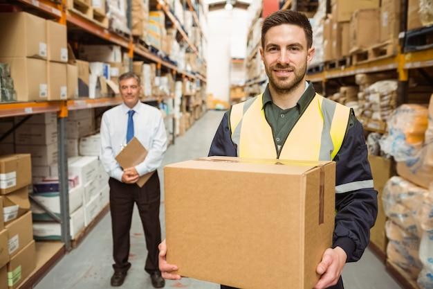 Trabalhador de armazém, sorrindo para a câmera, carregando uma caixa