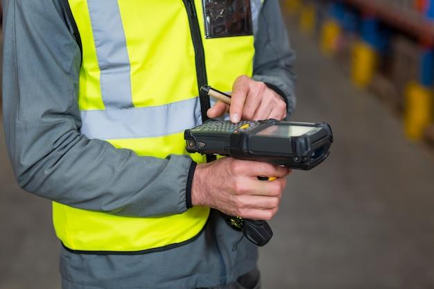 Trabalhador de armazém usando a máquina do scanner de código de barras