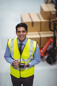 Trabalhador de armazém, usando o scanner de mão no armazém