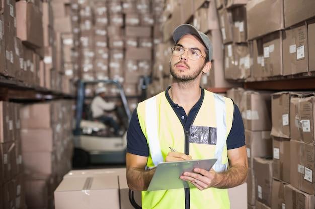 Trabalhador de armazém, verificando sua lista