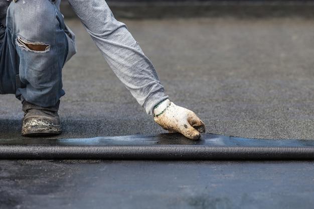 Trabalhador de ásia que instala a folha do alcatrão no telhado do edifício.