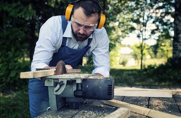 Trabalhador de barba com serra circular
