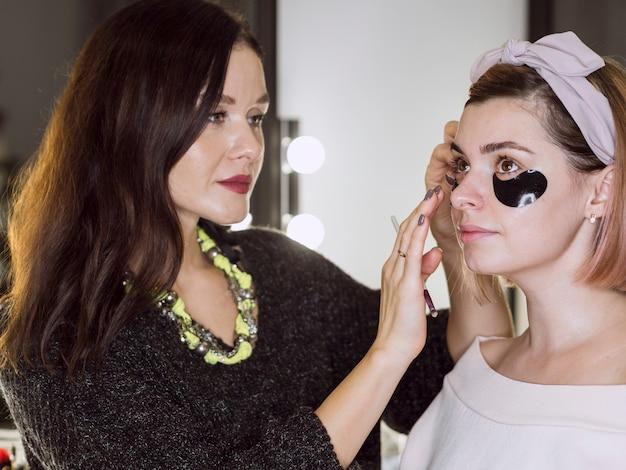 Trabalhador de beleza, aplicar a máscara no cliente