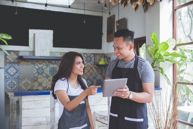 Trabalhador de café dois usando tablet juntos