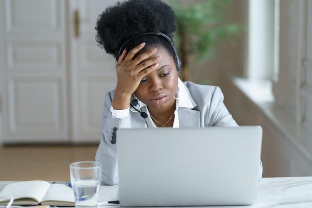 Trabalhador de call center de suporte feminino africano cansado com fone de ouvido frustrado parece chateado na tela do laptop
