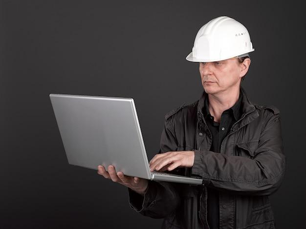 Trabalhador de camisa preta e terno segurando um laptop