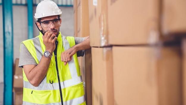 Trabalhador de carga profissional fala no rádio portátil para entrar em contato com outro trabalhador. conceito de comunicação de fábrica e armazém.