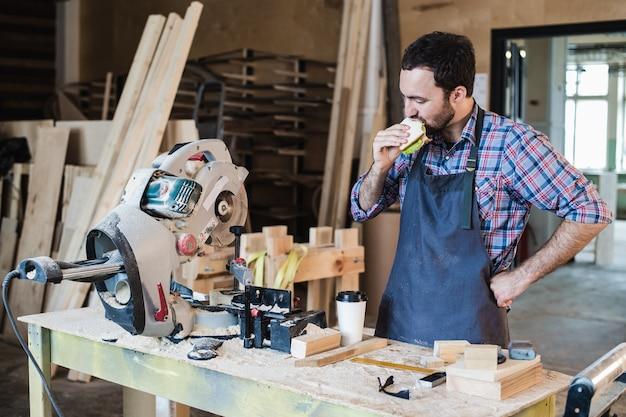 Trabalhador de carpintaria alegre almoçando e comendo sanduíche em uma oficina