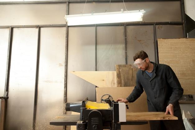 Trabalhador de carpintaria na maquina de espessura