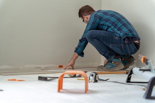 Trabalhador de carpinteiro instalando piso laminado na sala.