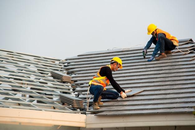 Trabalhador de carpinteiro no desgaste do trabalho de proteção especial e luvas, usando pistola pneumática e instalação de telha de telhado de concreto sobre o telhado novo, conceito de edifício residencial em construção.