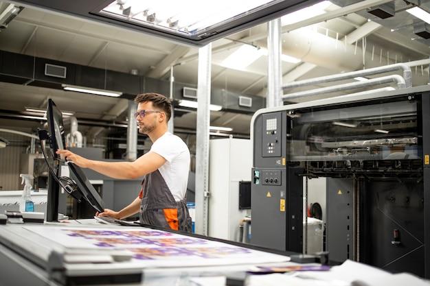 Trabalhador de casa de impressão definindo parâmetros na máquina de impressão offset moderna.
