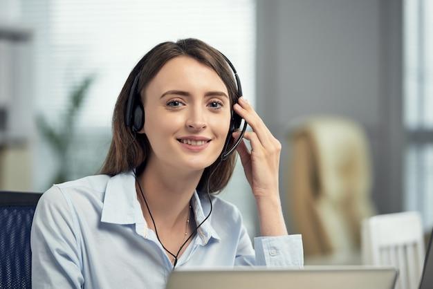 Trabalhador de centro de chamada feminina caucasiano feliz sorrindo no escritório