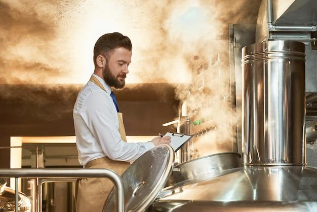 Trabalhador de cervejaria, segurando a pasta e inspecionando o processo de fermentação