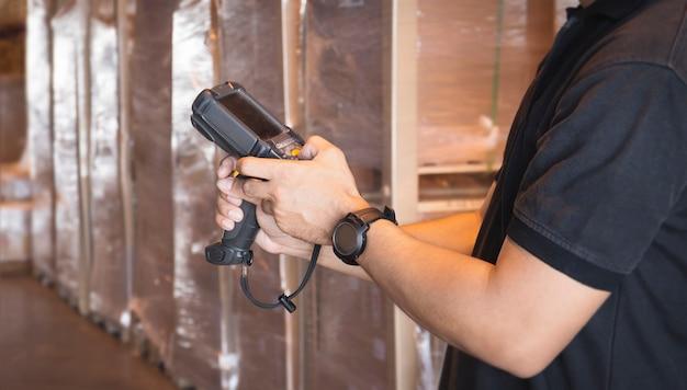 Trabalhador de close-up segurando o leitor de código de barras, seu inventário verificando o armazenamento do armazém. equipamento informático para gestão de armazéns.