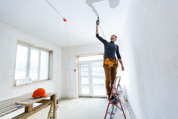 Trabalhador de construção com equipamento perfurador de martelo pneumático fazendo orifícios na parede do canteiro de obras