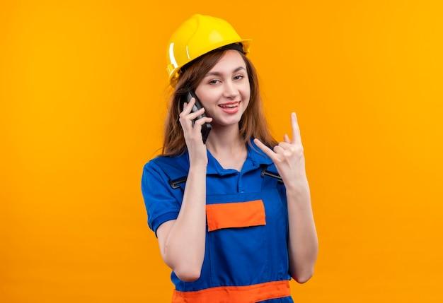 Trabalhador de construção jovem com uniforme de construção e capacete de segurança sorrindo enquanto fala no celular, fazendo o símbolo da rocha com os dedos em pé sobre a parede laranja
