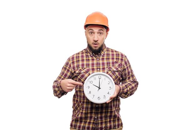 Trabalhador de construtor com raiva e chocado no capacete protetor de construção laranja segurando na mão um grande despertador isolado no fundo branco. hora de trabalhar. tempo de construção do edifício.