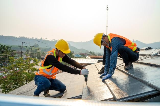 Trabalhador de construtor de telhados instalando telhado de cerâmica no topo do novo telhado no canteiro de obras.