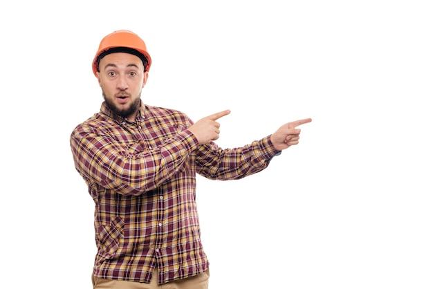 Trabalhador de construtor nas mãos de capacete laranja de construção protetora apontando para a direita, isolado no fundo branco. copie o espaço para o texto. hora de trabalhar.