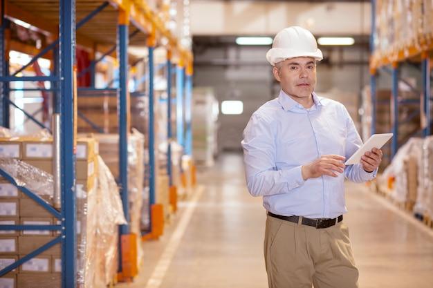 Trabalhador de depósito inteligente segurando um tablet enquanto verifica a segurança do depósito