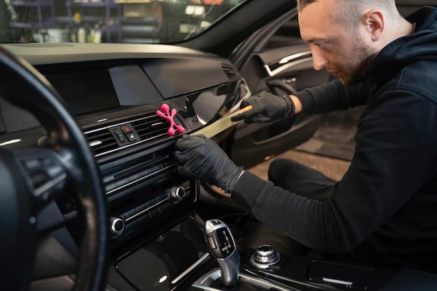 Trabalhador de detalhamento colando fita protetora no interior do carro