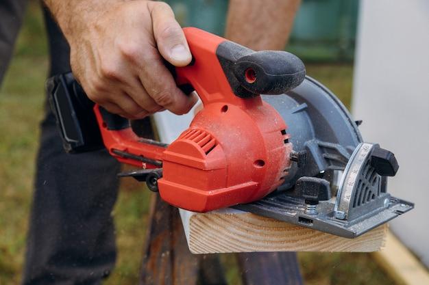 Trabalhador de empreiteiro usando a serra circular de mão para cortar placas em um novo projeto de construção de casas