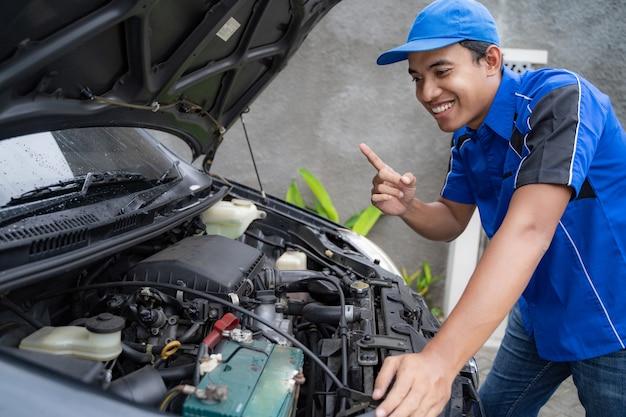 Trabalhador de engenheiro de carro uniforme azul, olhando para o motor do carro