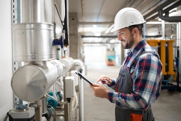 Trabalhador de engenheiro industrial segurando um computador tablet e definindo os parâmetros do sistema de aquecimento na sala da caldeira da fábrica.