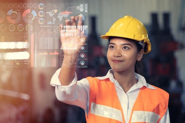 Trabalhador de engenheiro usando painel de toque de infográficos de holograma digital de tecnologia avançada na fábrica da indústria.