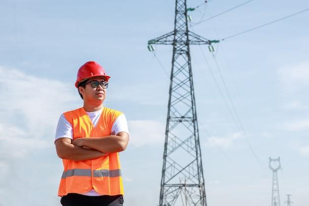 Trabalhador de engenheiros elétricos asiáticos com uniforme de segurança padrão em pé em uma estação de energia para inspecionar o poste de alta tensão de eletricidade.
