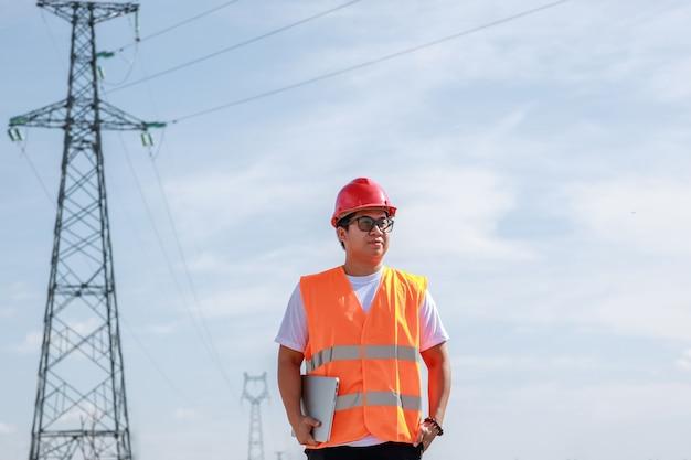 Trabalhador de engenheiros elétricos asiáticos com uniforme de segurança padrão, usando um móvel em pé em uma estação de energia para inspecionar o poste de alta tensão de eletricidade.