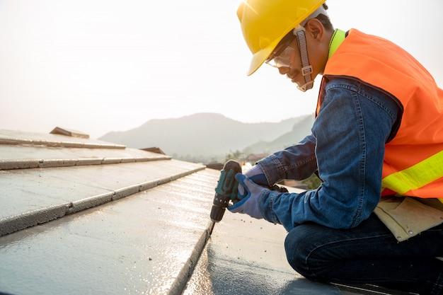Trabalhador de engenheiros instalar novo telhado cpac, ferramentas de cobertura, furadeira elétrica usada em novos telhados com telhado cpac, conceitos de construção.