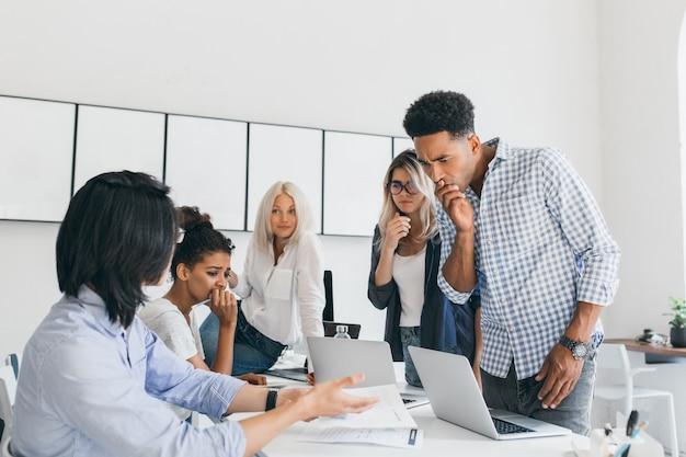 Trabalhador de escritório africano pensativo cobrindo a boca com a mão, enquanto resolve o problema com o computador. uma equipe de programadores da web asiáticos e negros encontrou um erro em seu projeto.