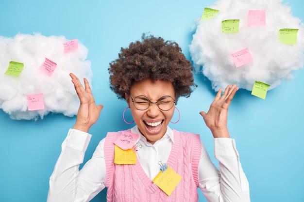 Trabalhador de escritório afro-americano encaracolado ocupado tem muitas tarefas ao mesmo tempo, exclama em pânico levanta as mãos preocupações sobre o prazo de entrega dentro de casa contra notas adesivas para lembrar todas as informações necessárias