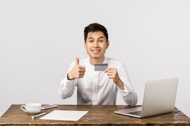 Trabalhador de escritório asiático bonito satisfeito, gerente sentado mesa com documentos, laptop e xícara de café, segurando o cartão de crédito, mostrar polegares para cima e sorrindo, recomendo comprar on-line e usar o serviço bancário