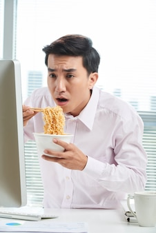 Trabalhador de escritório asiático na hora do almoço
