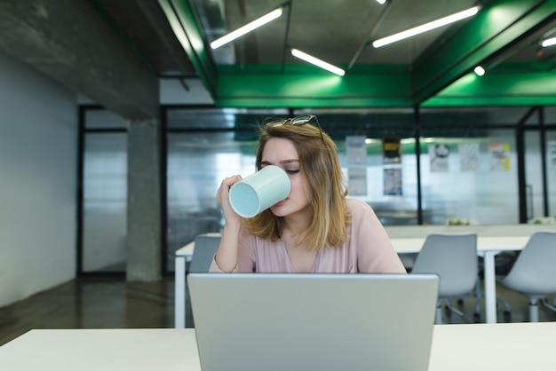 Trabalhador de escritório bebe café enquanto trabalhava em um computador.