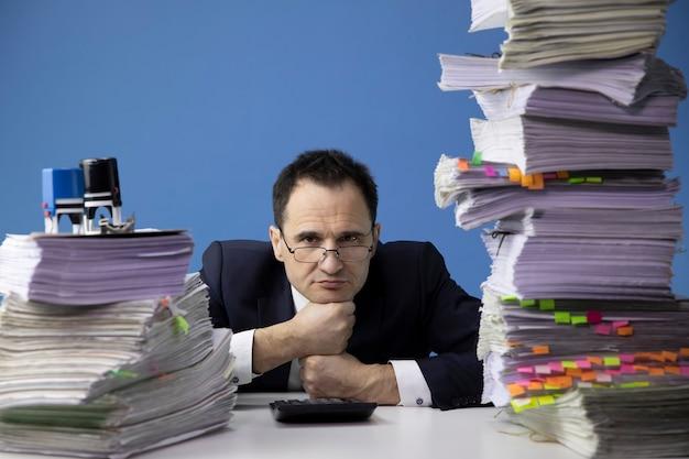 Trabalhador de escritório cansado coloca a cabeça nos punhos, cercado por altas pilhas de documentos