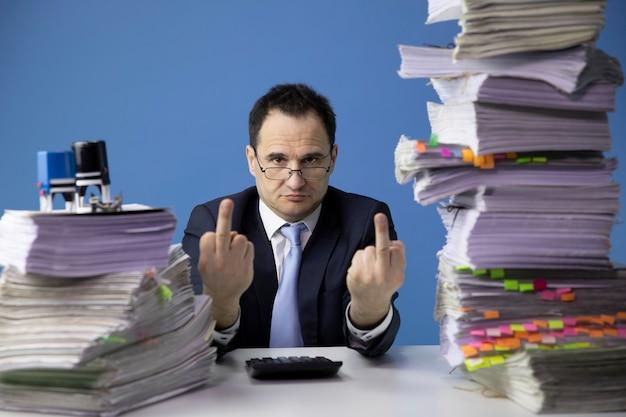 Trabalhador de escritório cansado, fazendo sinal com o dedo médio, sentado à mesa com uma pilha enorme de documentos