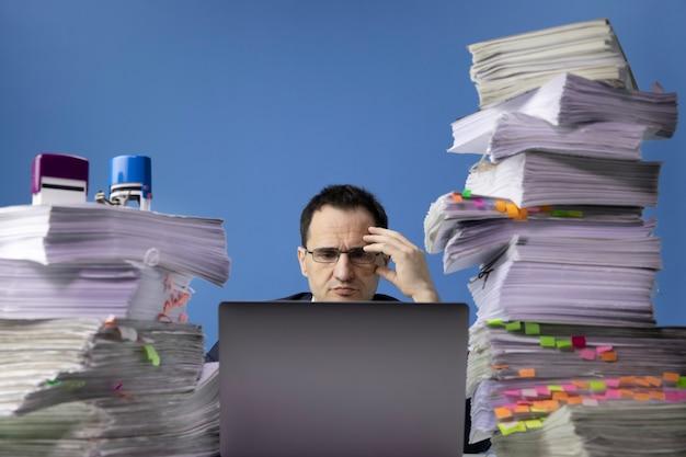 Trabalhador de escritório cansado usando um laptop e fazendo hora extra sentado na mesa com uma pilha enorme de papéis