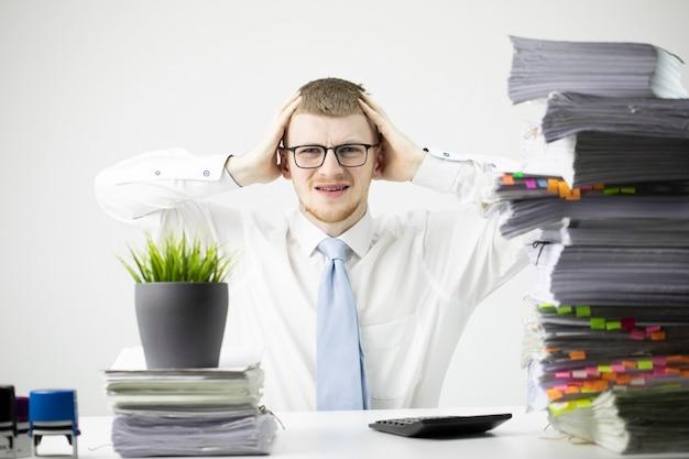 Trabalhador de escritório com camisa branca e tacha está segurando sua cabeça com as mãos e está desapontado