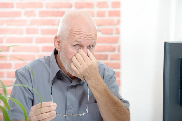 Trabalhador de escritório com dor nos olhos, tocando os olhos
