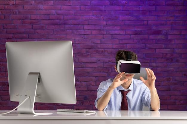 Trabalhador de escritório com visão frontal atrás de uma mesa de escritório jogando realidade virtual
