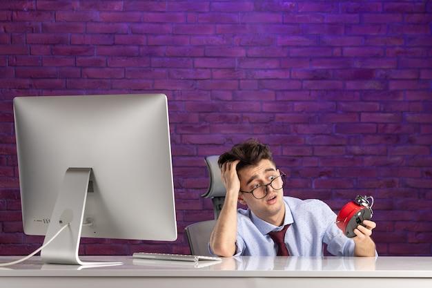 Trabalhador de escritório com vista frontal atrás de uma mesa de escritório segurando relógios